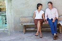 Couple sitting on wooden bench on patio