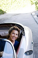 Woman in convertible car in driveway