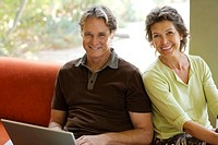 Man with laptop sitting beside woman in modern home