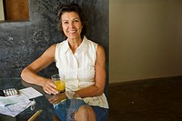 Woman sitting at a table with orange juice and paperwork