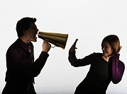 Businessman with bullhorn shouting at woman