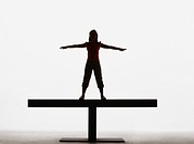 Small girl standing on a plank with arms out