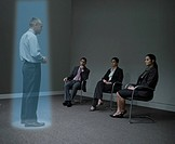 Three businesspeople watching a hologram of a businessman (thumbnail)