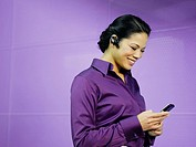 Businesswoman with mobile phone and earpiece in purple office (thumbnail)