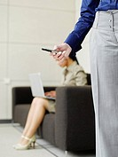 Businesswoman holding a mobile phone with coworker in background on laptop
