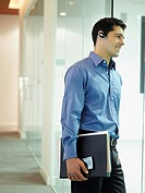 Businessman wearing headset in office hallway