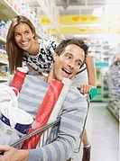 Woman pushing man in shopping cart