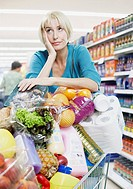Woman with shopping trolley full of groceries (thumbnail)