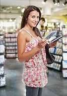 Woman looking at CDs with other shoppers in background
