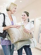 Woman and girl looking at pillows in store