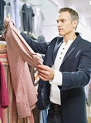 Man looking at shirt in store