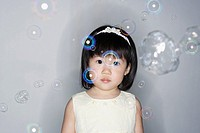 Girl standing with bubbles around her
