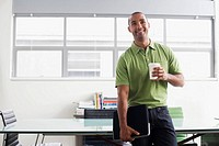 Businessman standing in office with coffee cup smiling