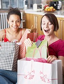 Two women with shopping bags in living room