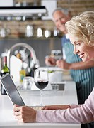 Man preparing food in kitchen while woman looks at laptop