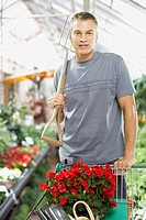 Man shopping for plants carrying pitchfork