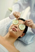 Woman lying on massage table having cucumbers placed over eyes