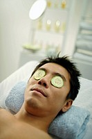 Man on massage table with cucumbers over eyes