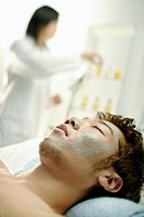 Man lying on massage table with mask drying on face