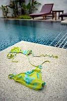 Woman´s bikini lying beside pool