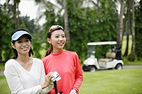 Two women by a golf cart on a golf course