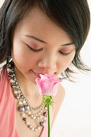 Woman smelling pink rose