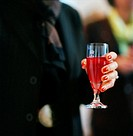 Woman´s hand holding a glass of Kir Royal