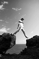 Man stepping across two rocks near ocean Black and white photograph