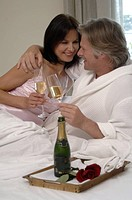 Couple in bed drinking sparkling wine