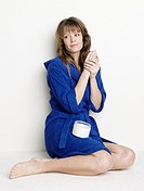 Woman in blue bathrobe using body cream (thumbnail)