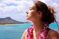 Hawaii, Oahu, Waikiki, Beautiful woman with eyes closed, orchid lei, Diamond Head background