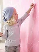 Blond girl wearing a headscarf is painting