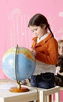 Girl standing next to a globe