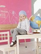 Blond girl wearing a headscarf sitting on the table next to globe