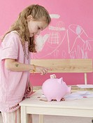 Girl is putting money in a piggy bank