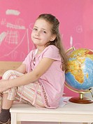 Girl sitting next to a globe