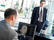 Biometric face scanning  Man top right having his face screened by a biometric scanner  This scanner is being used to identify him from his facial con...