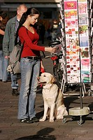 Labrador in the city - with woman in front of kiosk