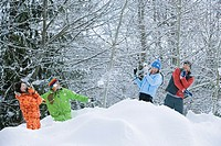 Two young couples having snowball fight near forest