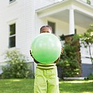Young girl 8-9 years holding ball over face, house in background