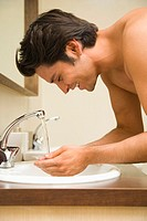 Man washing face in bathroom, profile