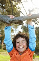 Boy 7-9 hanging on branch in park, portrait