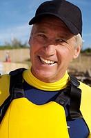 Mature man wearing lifejacket outdoors, smiling, portrait