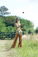Young woman standing in field, juggling apples