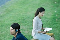 People sitting in park, man listening to headphones while woman reads book