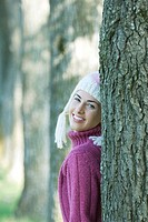 Young woman wearing knit hat, leaning against tree, smiling over shoulder at camera