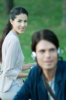 People sitting in park, man listening to headphones, woman smiling at camera