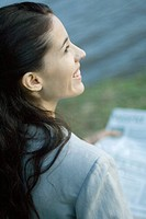 Woman holding newspaper, smiling, over the shoulder view