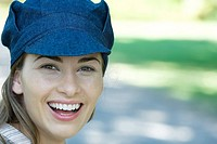 Young woman wearing cap, smiling at camera, portrait
