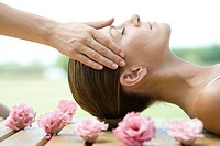 Woman lying on deck, surrounded with flowers, having head massage